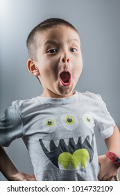 Mixed race 5 year old boy with scary face and monster shirt