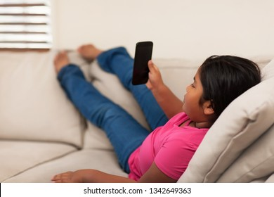 Mixed race 8 year old girl watching mobile phone while stretching out her legs; sitting on a couch with a relaxed pose.