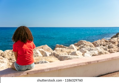 Mixed race African American girl teenager female young woman wearing a red t-shirt and denim shorts sitting on a wall looking out to a blue sea