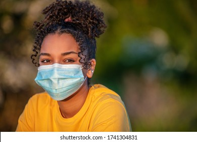 Mixed race African American teenager teen girl young woman wearing a face mask outside during the Coronavirus COVID-19 virus pandemic - Shutterstock ID 1741304831