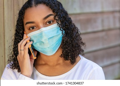 Mixed race African American teenager teen girl young woman wearing a face mask and talking on mobile cell phone during the Coronavirus COVID-19 pandemic
