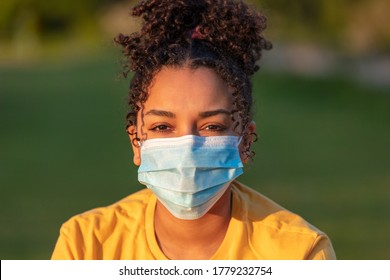Mixed race African American teenager teen girl young woman wearing a face mask outside during the Coronavirus COVID-19 pandemic