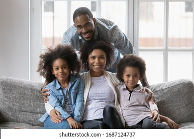 Mixed race African ethnicity full family gathered together in living room photo shooting look at camera, happy family portrait, first new home, loan and mortgage, next generation and adoption concept