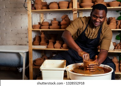 mixed race afro male potter with black apron and stylish dark shirt sitting at workshop table potter's wheel , applying glaze on handmade clay brown pot vase