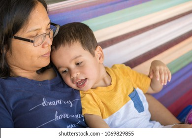 Mixed race asian caucasian boy plays with his mother in a colorful hammock