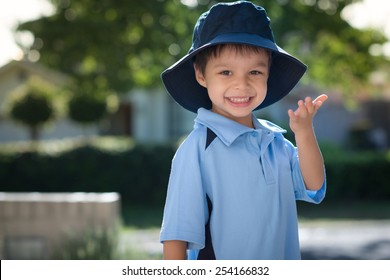 Mixed race Asian Caucasian boy confidently leaves home on his first day of school. Wearing uniform and sun hat. Turning to blow a kiss to his mom as he leaves his house.