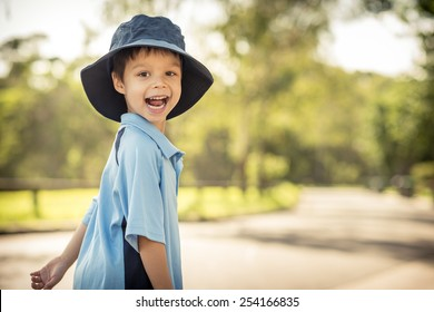 Mixed race Asian Caucasian boy confidently leaves home on his first day of school. Wearing uniform and sun hat. Walking down his suburban street in the summer sun
