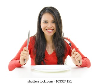 Mixed race Asian woman holding fork and knife with an empty plate ready for food, isolated on white background