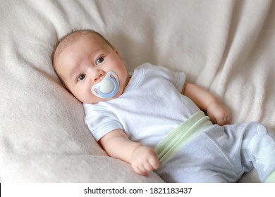Mixed race Asian-German newborn baby lying on bed sucking pacifier on his mouth. Cute infant boy about 1-2 months old relaxing at home.