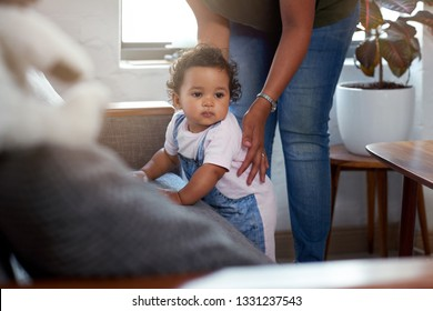 Mixed race baby girl cruising along sofa couch supported by mom, learning how to walk move growing developement skill