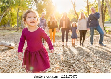Mixed Race Baby Girl Outdoors with Family Behind.
