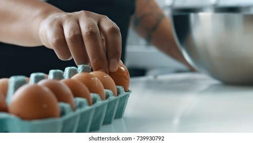 mixed race baker makes a cake. smash eggs