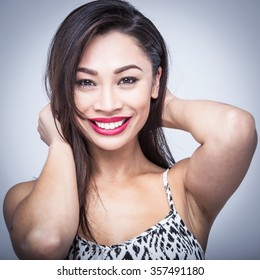Mixed race beauty with big red lips and white teeth in studio portrait.