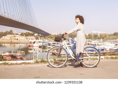 Mixed race black woman with bicycle enjoying free time near river.