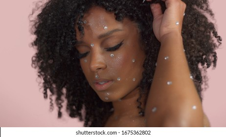 Mixed race black woman with curly hair covered by crystal makeup