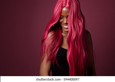 mixed race black woman with pink hair happy smiling. creative hair colour