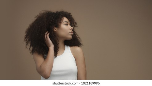 mixed race black woman portrait with big afro hair, curly hair in beige background Touching her hair