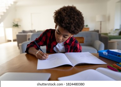 Mixed race boy, social distancing and self isolation in quarantine lockdown, sitting by a table, drawing in a drawing book