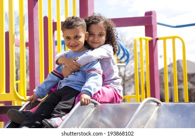 mixed race brother and sister hugging and smiling