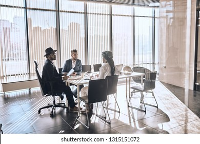 mixed race business people chatting in modern office. management concept. copy space