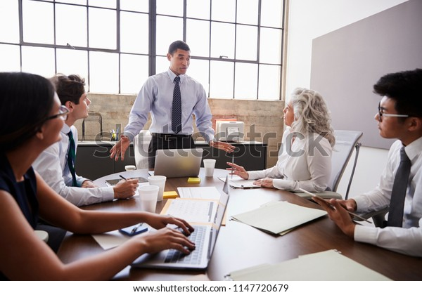 Mixed race businessman stands addressing team in a meeting