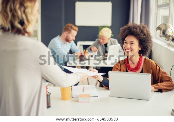 Mixed race businesswoman sitting in modern office and working on laptop while coworker giving her paperwork