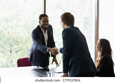 Mixed race and Caucasian business partners start group meeting shake hands express regard. Happy candidate get hired job interview accomplish. Gesture of approval acceptance, business promises concept