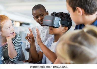 Mixed race child with vr virtual reality goggles in classroom. Multiethnic pupil having fun with virtual reality headset at elementary school. Happy boy gesturing while using VR headset in classroom.