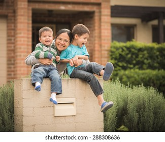 Mixed race children with their Asian mother play in front of their family home. Image captures family love, confidence, cheerfulness, and togetherness at home.