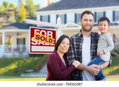 Mixed Race Chinese and Caucasian Parents and Child In Front of House and Sold For Sale Real Estate Sign.