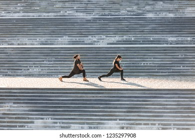Mixed race, a couple of athletes are simultaneously engaged in stretching on large steps in an urban environment on a sunny summer day. Healthy lifestyle concept. Place for your advertising content