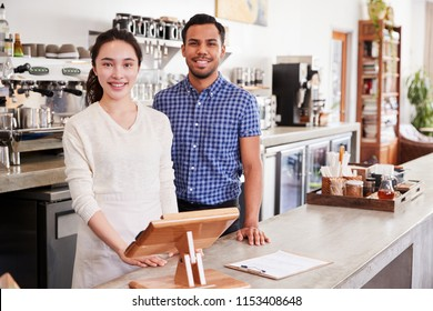 Mixed race couple behind the counter at their coffee shop
