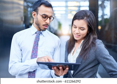 Mixed race couple of co-workers reviewing social media strategy with a tablet