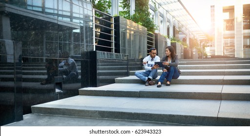 Mixed race couple of co-workers reviewing social media strategy on stairs with a tablet