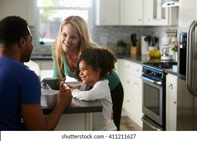 Mixed race couple and daughter talk together in the kitchen