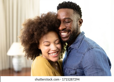 Mixed race couple enjoying their time at home together, standing by a couch, embracing and smiling, social distancing and self isolation in quarantine lockdown during coronavirus covid19 epidemic