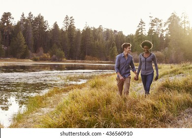 Mixed race couple holding hands, walking near a rural lake