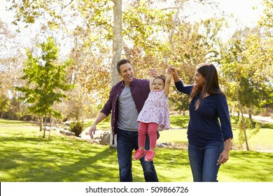 Mixed race couple lifting up their young daughter in park