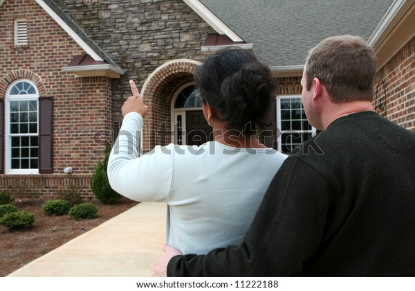 Mixed race couple looking at houses to buy