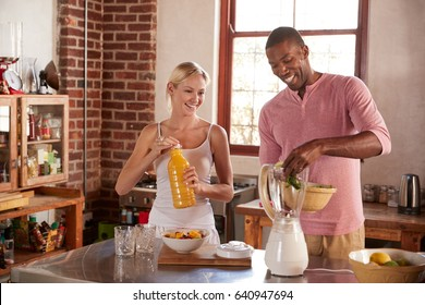 Mixed race couple making smoothies together at home