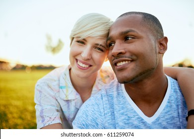 Mixed race couple of millennial in a grass field embracing for a fun tender moment