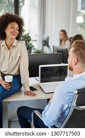Mixed race employee sitting on table with coffee in hand and talking to CEO. Man sitting in chair with backs turned. In background other employees working.