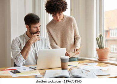 Mixed race family couple examine paperwork, plan familly budget, ask advice each other, pose against cozy domestic interior near window, use laptop computer, drink takeaway coffee. Cooperation concept