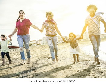 Mixed race family friends running and having fun on the beach - Diverse culture parents and children enjoying time together - New multi ethnic families and travel concept - Main focus on right people