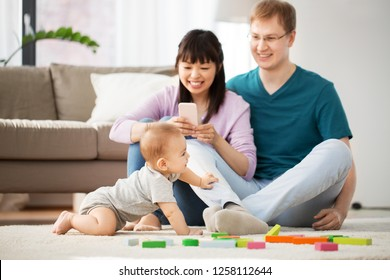 mixed race family, parenthood and people concept - happy mother with smartphone, father and baby boy playing toy blocks at home