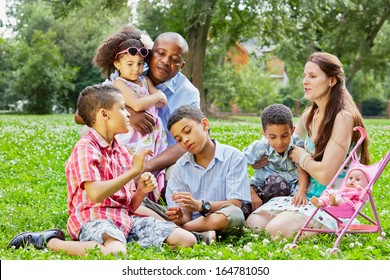 Mixed race family of six rests sitting on grass in summer park