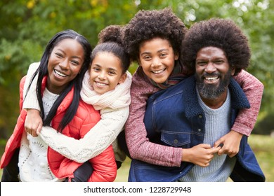 Mixed race family smiling to camera, parents piggybacking kids in the countryside, close up