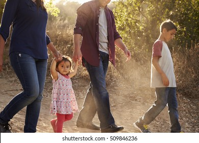 Mixed race family walking on rural path, close up side view