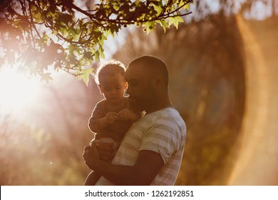 Mixed race father carrying his young son in a park, loving tender moment