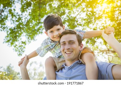 Mixed Race Father and Son Playing Piggyback Together in the Park.